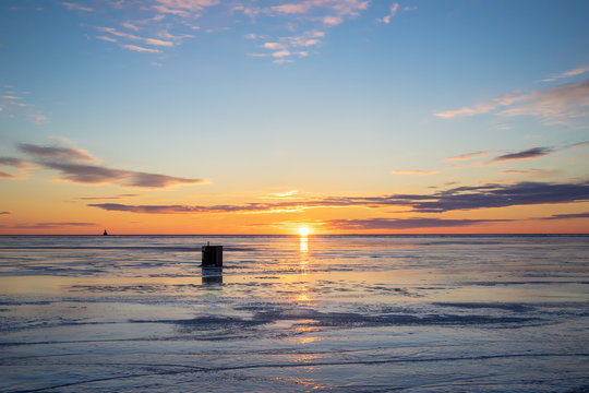 The sun setting over a frozen harbor and an ice fishing shack in rural Prince Edward Island, Canada. Lighthouse on the horizon.......