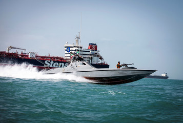 A boat of the Iranian Revolutionary Guard sails near to Stena Impero, a British-flagged vessel owned by Stena Bulk, at an undisclosed place at sea of Bandar Abbas