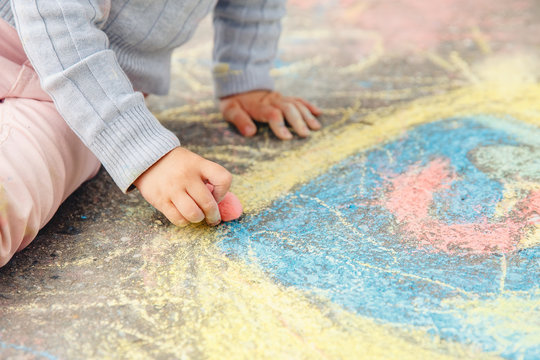 Child draws hand in colored chalk drawing on pavement. Top view