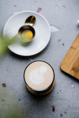 Masala chai latte with honey and vegan candy from above on light gray concrete table. Coffee shop, food photography concept, copyspace