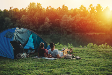 Fototapeten Camping young couple relaxing by the river. camping outdoor