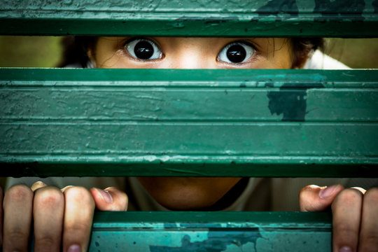Closeup of eyes of girl,asian child sneak peek,peeping eyes,feel afraid fear,frightened or saw something scary with fixed eyes,stare dumbfounded hiding looking at camera,mental disorder,mistrust