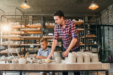 Attractive caucasian man and liitle cute boy kneading clay for pots.