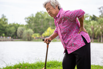 Asian senior woman with hip joint pain while walking ,female patient having backache,lumbago pain,hands touching on the hip,elderly people suffering from ribbing pain or waist pain,health problems