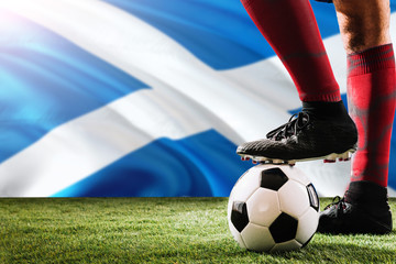 Close up legs of Scotland football team player in red socks, shoes on soccer ball at the free kick or penalty spot playing on grass.