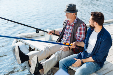 Recess Fitting Water Motor sports Bearded retired man sitting near son and catching fish