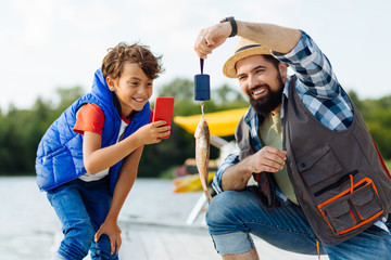 Cheerful boy taking picture of fish while fishing with dad