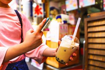 [原宿文化イメージ] 流行に敏感な少女がタピオカミルクティーを買ってスマホでSNSに投稿するシーン