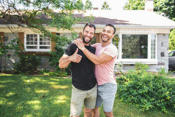 A Portrait of a happy gay couple outdoors in front of a new buy