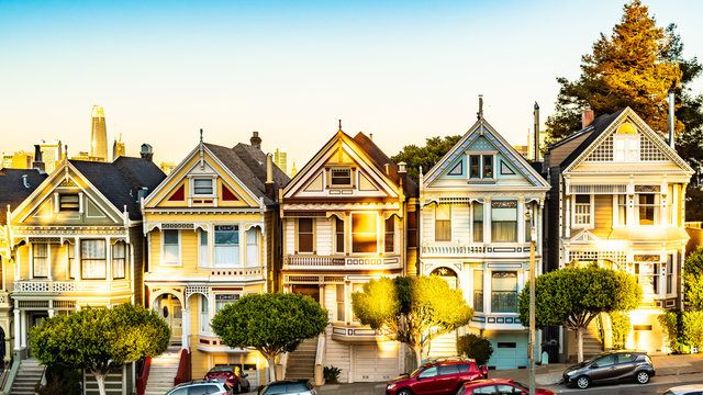 Row of charming colored Victorian style homes on the incline of the hills of San Francisco city, California. Front exterior view of beautiful houses. Modern architecture with vintage design appeal.