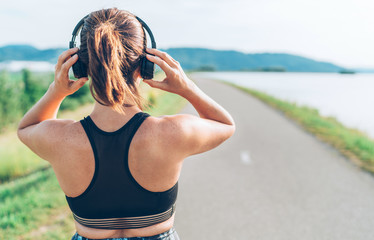 Young teenager girl adjusting  wireless headphones before starting jogging and listening to music