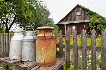 Old milk cans in The Folk Culture Museum in Osiek by the river Notec, the open-air museum presents polish folk culture. Poland, Europe