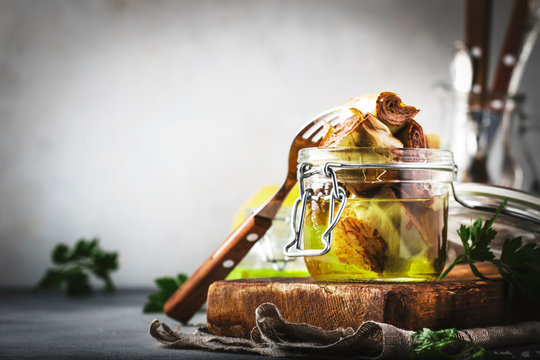 Italian appetizer canned Artichokes in olive oil in glass jar with lemon and herbs on gray kitchen table background, copy space,  selective focus