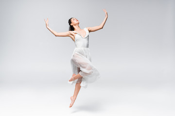 young elegant ballerina in white dress dancing on grey background