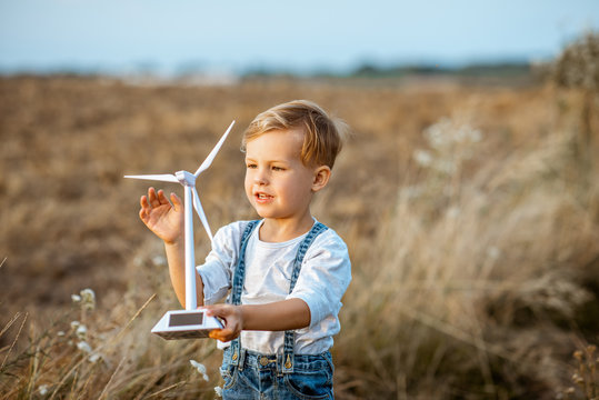 Curious young boy playing with toy wind turbine in the field, studying how green energy works from a young age