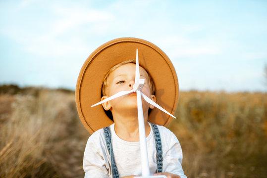 Boy with wind turbine model in field