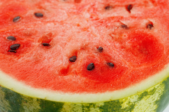 Half of juicy, red watermelon on a white background, texture of juicy pulp and mesmeses of ripe watermelon