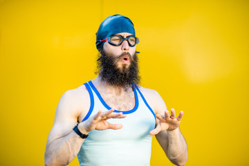 Portrait of a weird, old-fashioned swimmer dressed in 80s style with hat and swimming glasses on the yellow background Wall mural