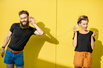 Man and woman talking with string phone made of cups on the yellow background. Concept of broken phone and bad communication