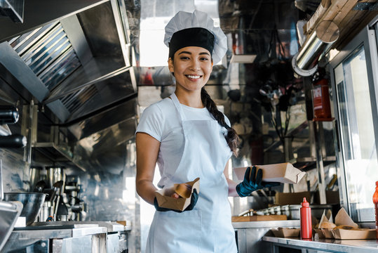 happy asian chef holding carton plates in food truck