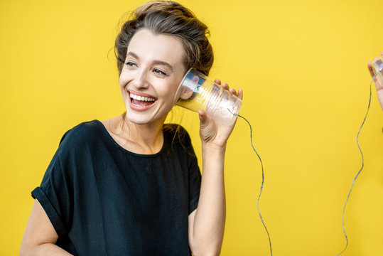 Happy woman listening to a cup, using string phone on a yellow background. Concept of communication and listening