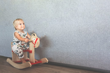 Cute blond baby rides wooden toy horse near big grey wall
