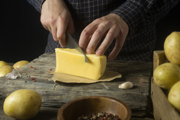 Man cuts cheese in the kitchen on a rustic wooden table