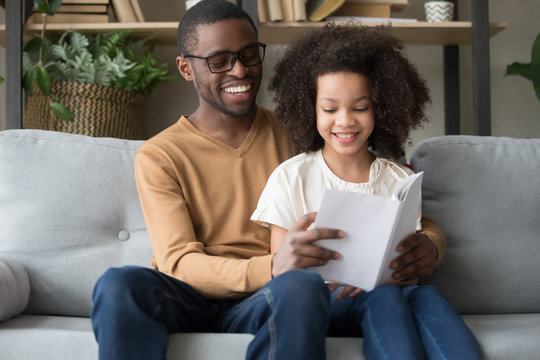 Happy African American father with preschool daughter reading book