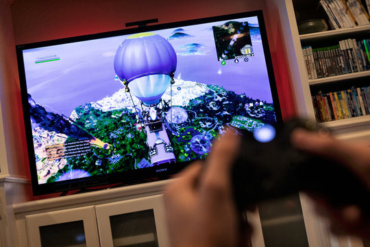 St. Louis, Missouri, USA - August 17, 2019: Anonymous Gamer Playing Fortnite Game On Xbox One System