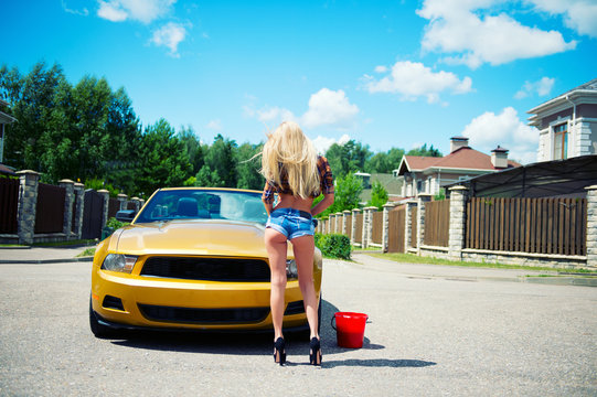 Young blond sexy model girl ready to wash golden luxury car with foam outdoors