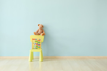 Chair with teddy bear and abacus near color wall in children's room Fototapete