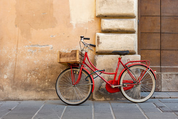 Red classic model women's bicycle with a lock parked against the wall in the Italian city of Foligno.