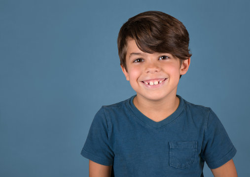 Handsome happy smiling boy in blue shirt isolated on blue background