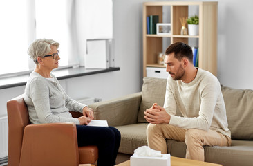 psychology, mental therapy and people concept - senior woman psychologist talking to sad young man patient at psychotherapy session