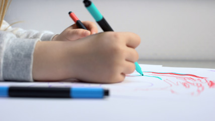 Child drawing with colored pencils, art therapy for children, rehabilitation