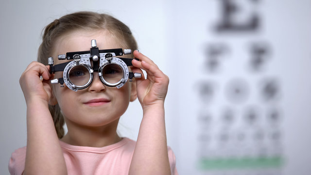 Pretty girl in optical trial frame smiling seeing clearly, vision correction
