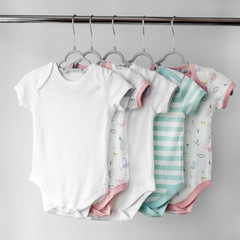 A set of beautiful clothes for a newborn girl on hangers. The concept of clothes, motherhood, fashion and newborn.