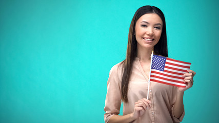 Cheerful girl holding USA flag, ready to learn foreign language, English school