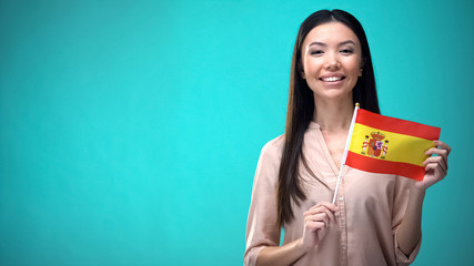 Cheerful girl holding Spain flag ready to learn foreign language, Spanish school