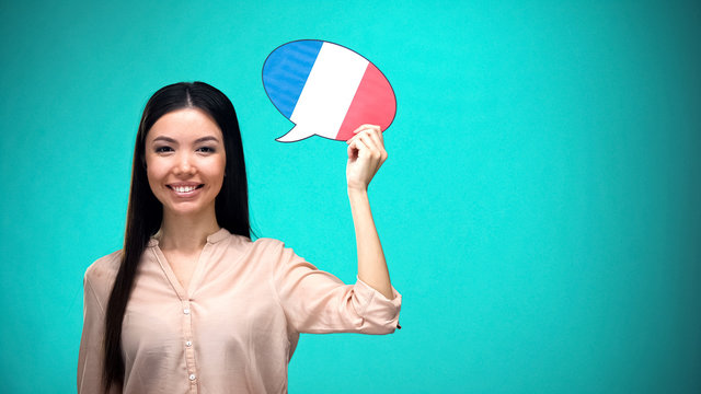 Smiling girl holding French flag speech bubble, learning language, travel ideas