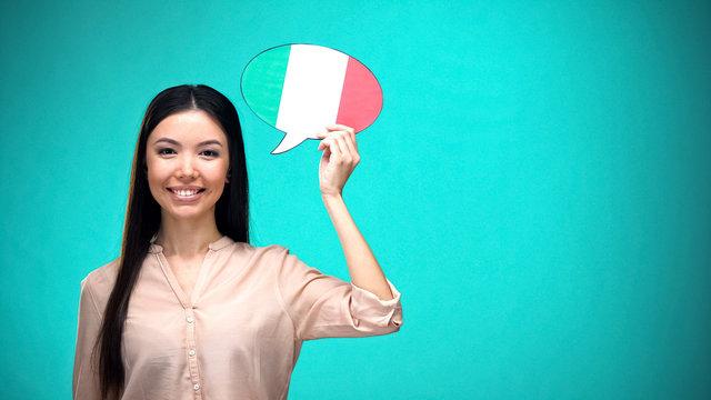 Smiling girl holding Italian flag speech bubble, learning language, travel ideas