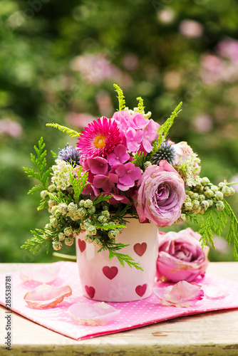 Colorful flower bouquet in a coffee cup