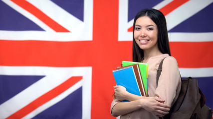 Fototapeta Cheerful Asian woman standing against British flag background, study abroad obraz