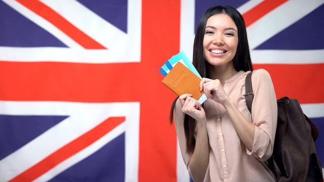 Happy female traveler holding passport with flight tickets against British flag