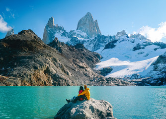 Couple in love at Mount Fitzroy. Scenic view of snowcapped mountain tops of Patagonia trek. Blue sky, turquoise lake and scenic rock landscape. Shot in Argentina. Nature, travel, adventure, hiking. Fotomurales