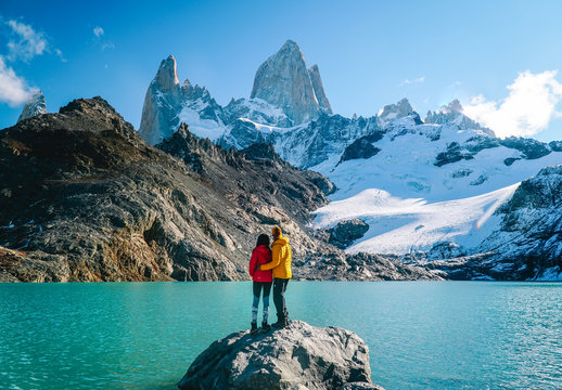 Couple in love at Mount Fitzroy. Scenic view of snowcapped mountain tops of Patagonia trek. Blue sky, turquoise lake and scenic rock landscape. Shot in Argentina. Nature, travel, adventure, hiking.