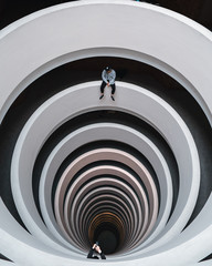 Tow people across from each other on a spiral walkway.