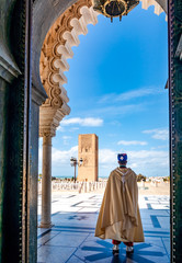 Door stickers Morocco Guard soldier in national costume at the entrance of Mausoleum of Mohammed V and square with Hassan tower in Rabat on sunny day. Location: Rabat, Morocco, Africa