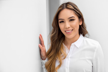 Head shot of a mixed ethnicity young hispanic woman, smiling genuine lifestyle portrait on white background