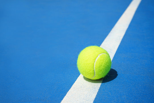 Summer sport concept with tennis ball on white line on hard tennis court blue color.